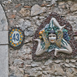"""Например, древний знак """"Трискелион"""" в виде трех бегущих ног с головой Медузы в центре украшает сицилийский флаг, а также изображается на стенах и воротах Таормины"""